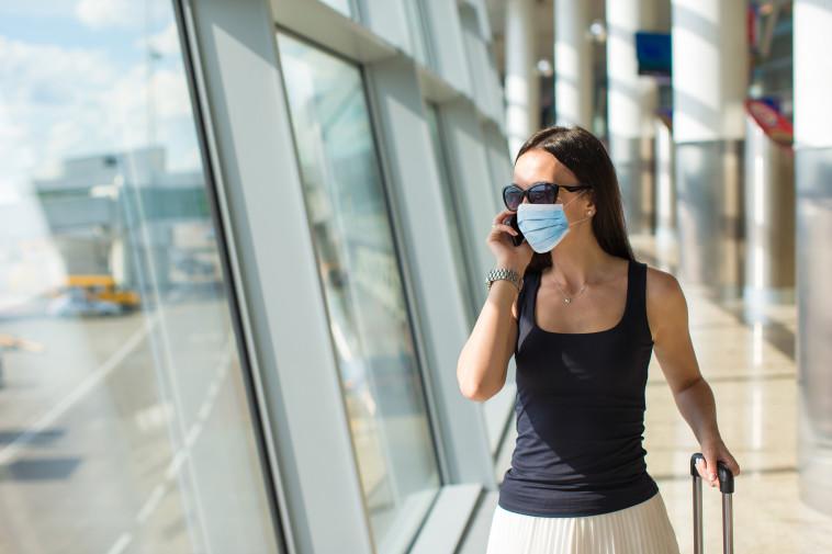 אישה במסכה בנמל תעופה (צילום: אינג אימג')