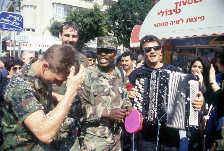 פורקים מתח: שרים וצוהלים ברחוב עם חיילים אמריקאיים (צילום: באדיבות ארכיון צה''ל במשרד הביטחון,אלכס ליבק)