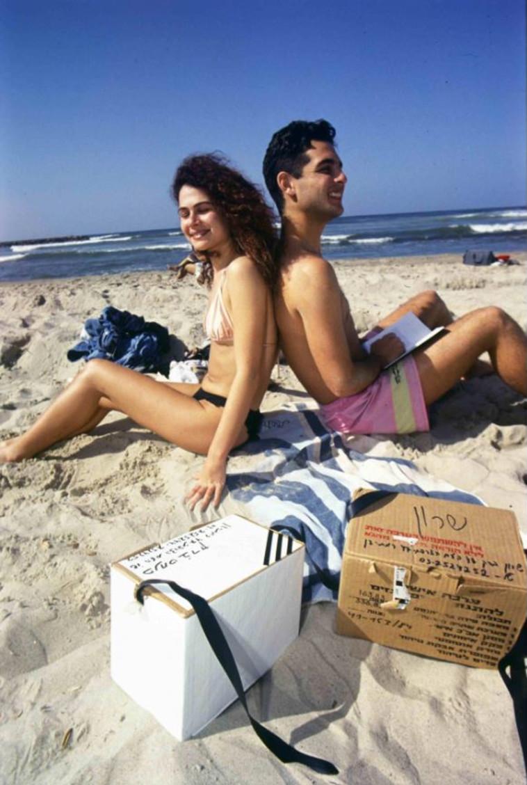 תופסים שמש: על חוף הים, עם הקופסאות של המסכות ליתר ביטחון (צילום: נעם וינד,באדיבות ארכיון צה''ל במשרד הביטחון)