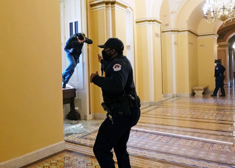 שוטרים אמריקאים מרססים בספרי פלפל את המפגינים שפרצו לבניין הקפיטול (צילום: Kevin Dietsch/Pool via REUTERS)
