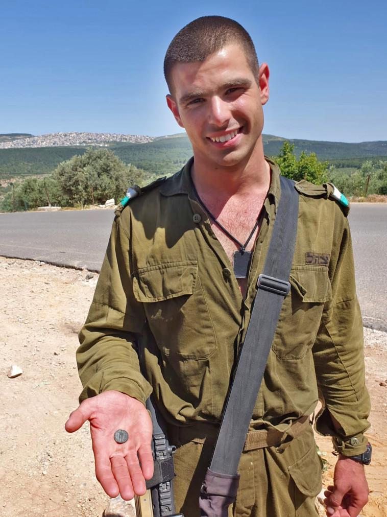 החייל עידו גרדי עם המטבע הנדיר (צילום: ניר דיסטלפלד, רשות העתיקות)