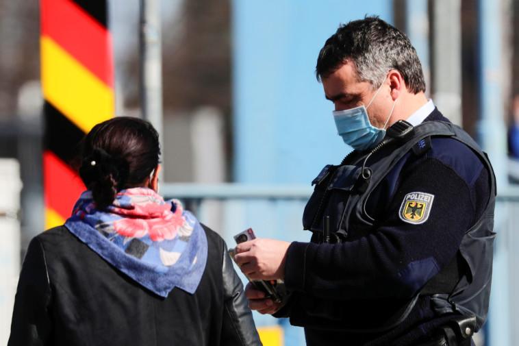 שוטר גרמני בודק אישה שהגיעה מפולין  (צילום: REUTERS/Hannibal Hanschke)