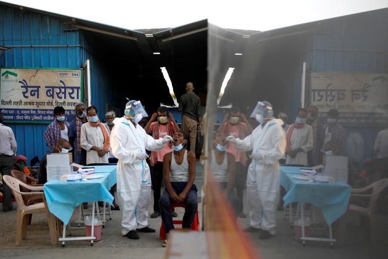 בדיקות קורונה מבוצעות בניו דלהי, הודו (צילום: REUTERS/Adnan Abidi)