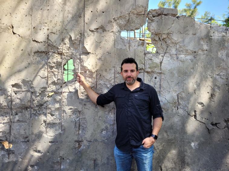 עו''ד רועי ברזילי על רקע חומת תצוגת קופי האורנגאוטן שנפגעה (צילום: שגית הורביץ', דוברת הספארי)