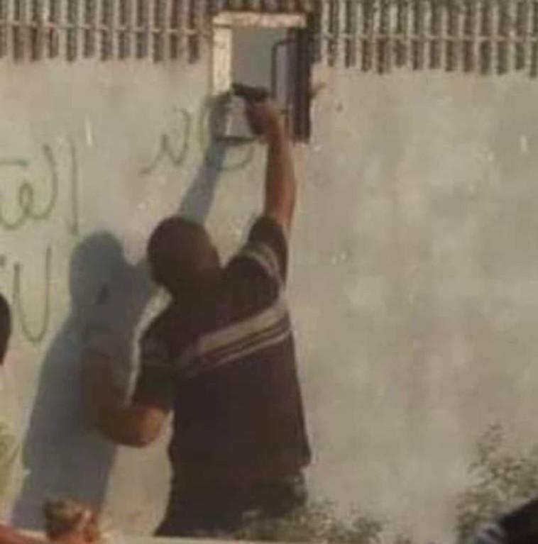 מפגין פלסטיני מכוון אקדח דרך גדר רצועת עזה (צילום: ללא)