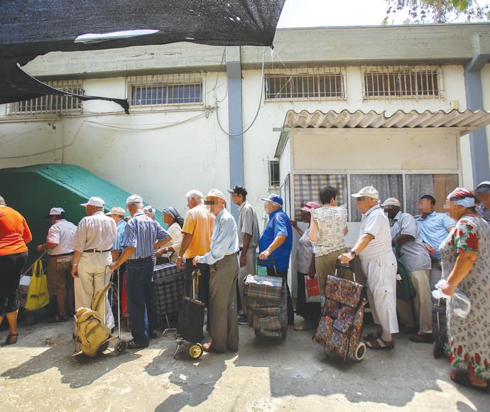 נזקקים עומדים בתור לחלוקת מזון