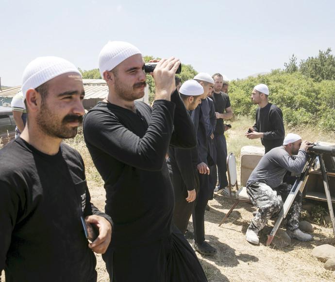 דרוזים בצד הישראלי של הגבול משקיפים על הלחימה בכפר הדרוזי חאדר בצד הסורי