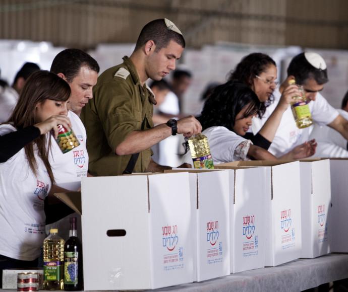 מתנדבי מבצע חג שבע לילדים מכינים אריזות מזון לחג