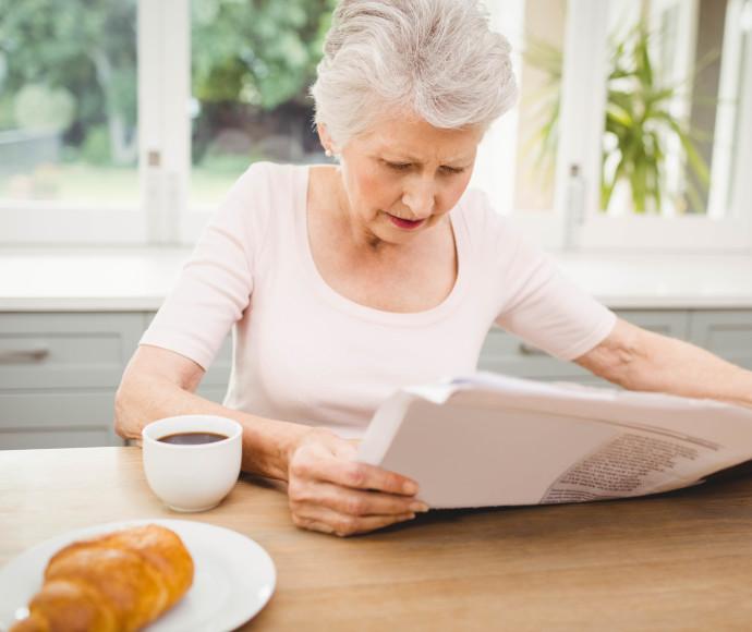 אישה מבוגרת קוראת עיתון, צילום אילוסטרציה