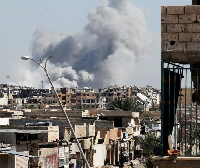 עשן עולה לאחר הפצצה בעיר הסורית א-ראקה