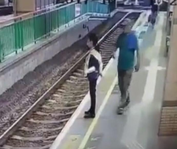 גבר דוחף אישה לפסי הרכבת