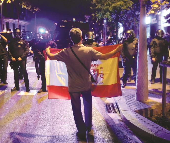 אדם מחזיק דגל קטלוניה מול שוטרים בברצלונה