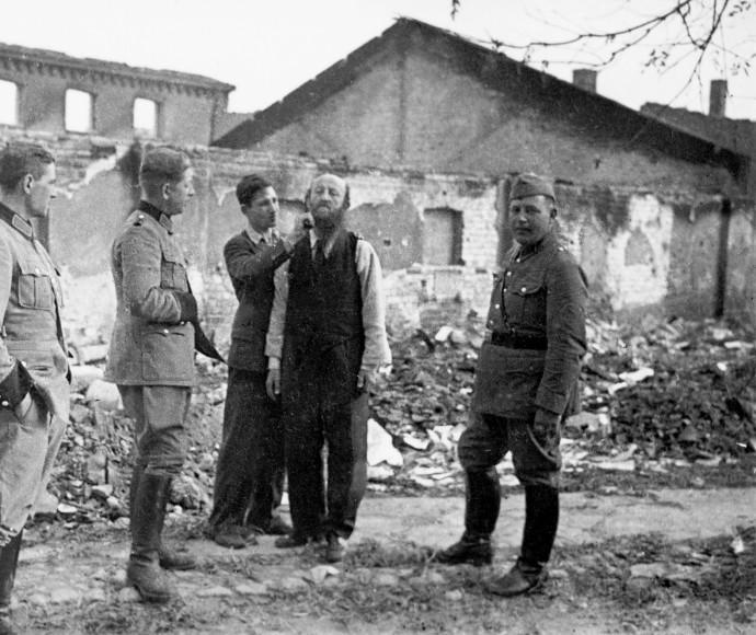 פולני מגלח ליהודי את שערו בפני חיילים גרמנים, 1939