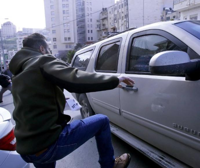 מפגין פלסטיני בועט ברכב אמריקאי בבית לחם