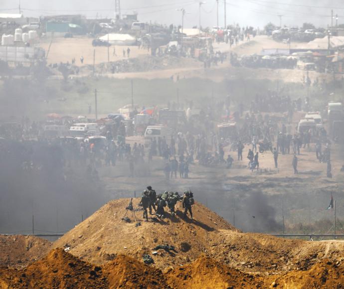 חיילים ישראלים ופלסטינים על הגדר בגבול עזה-ישראל