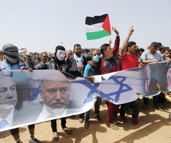 פלסטינים בעזה מפגינים עם תמונות נתניהו וליברמן