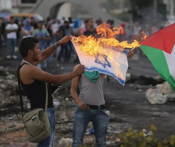 מפגינים פלסטינים שורפים דגל ישראל ליד בית אל