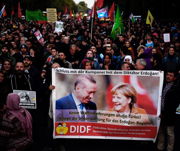 """מפגינים מניפים שלט בו כתוב """"די לתמיכה הגרמנית בארדואן"""""""