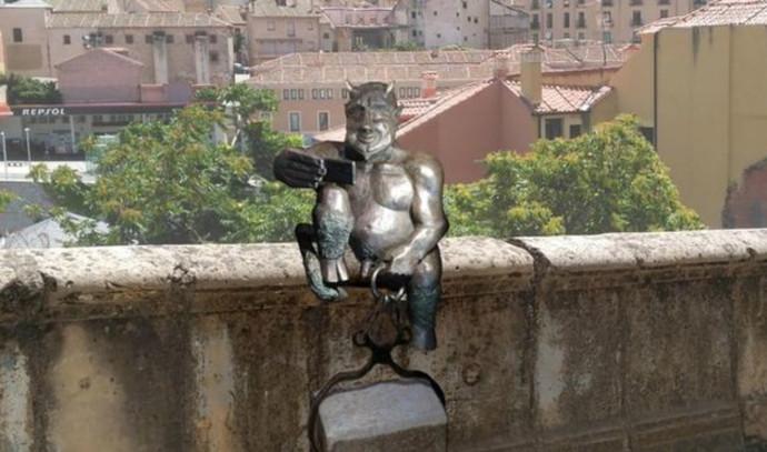 פסל של שטן מצלם סלפי מעורר מחלוקת בספרד