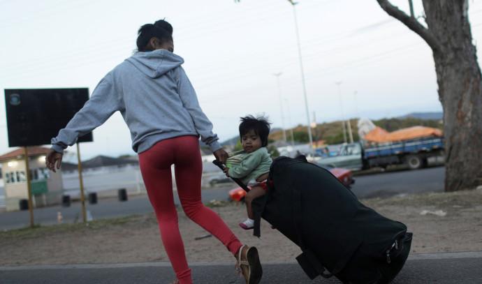 אישה המבקשת לחצות את הגבול מוונצואלה לברזיל לוקחת עמה את בנה על מזוודה