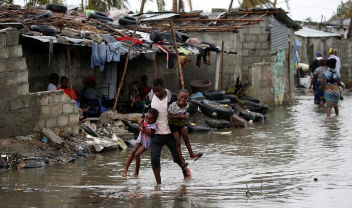 גבר נושא את ילדיו באזור האסון בעיר ביירה, מוזמביק