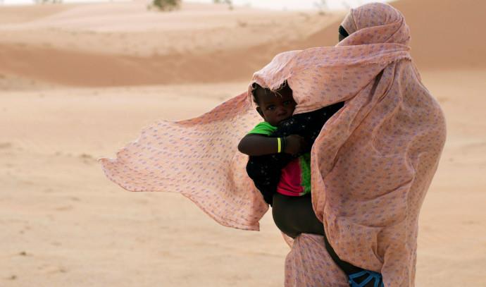 אישה מגנה על בנה מפני הרוח במאוריטניה, מערב אפריקה