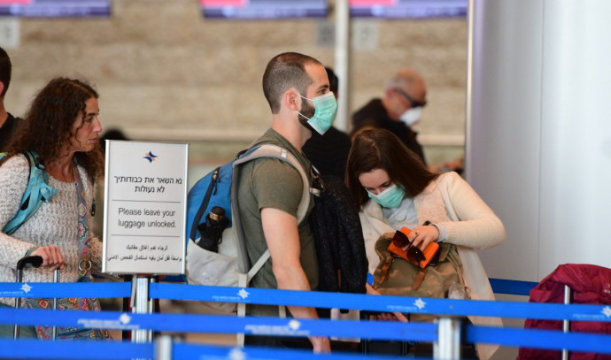 """נגיף הקורונה: ישראלים עוטים מסכות בנתב""""ג"""