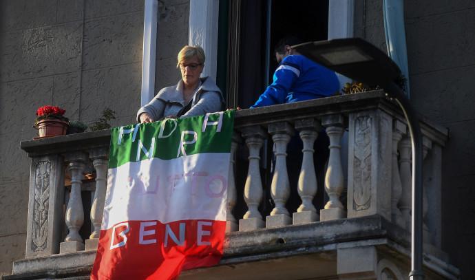 """קורונה באיטליה: אישה מניחה את דגל איטליה עם הכיתוב: """"הכל יהיה בסדר"""" על מרפסת ביתה"""